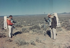 Two men with large backpacks stand amid a desert landscape