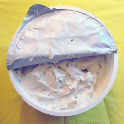 Open package of a soy-based cream cheese alternative with chives