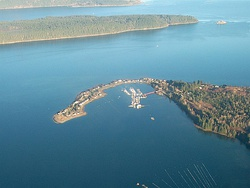 Aerial view of Deep Bay Marina with Baynes Sound, Denman Island (Chrome Island Light off its tip) and Hornby Island in the background.