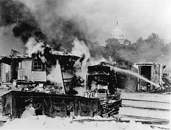 Shacks on the Anacostia flats, Washington, D.C. put up by the Bonus Army (World War I veterans) burning after the battle with the 1,000 soldiers accompanied by tanks and machine guns, 1932[172]
