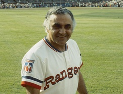 "A man in a white baseball uniform with ""Rangers"" on the chest in red"