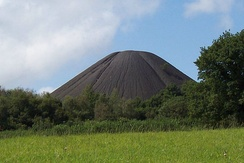 Large conical black mound with trees in the foreground