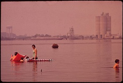 Swimming in polluted Lake Charles opposite the Olin Mathieson chemical plant in 1972.  Cleanup efforts of Lake Charles' waterways have been so successful that Prien Lake now supports both recreational and commercial fishing, and has a safe public beach.[21][22]