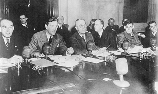 Senators, counsel, witnesses, and visitors at a 1943 meeting of the Truman Committee. Senator Harry S. Truman is at the center.