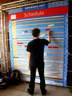 A volunteer adjusts the schedule board at Wikimania 2007. The board indicates the times and locations at which events will take place, thus assisting participants in deciding which events they can attend.