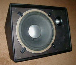 "A JBL floor monitor speaker cabinet with a 12"" woofer and a ""bullet"" tweeter. Typically, the speaker would be covered with a metal grille to protect it."