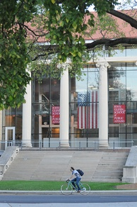 A photo of the John Glenn College of Public Affairs, with an American flag hanging inside and a cyclist riding past the stone steps