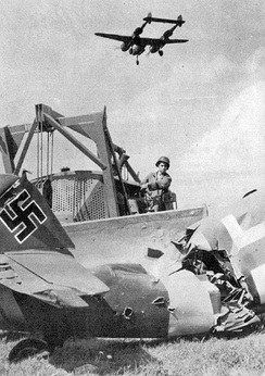 A USAAF Engineer clearing out the wreckage of a destroyed Luftwaffe Bf 109 aircraft at an ALG, with a P-38 Lightning flying overhead on landing approach
