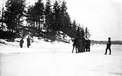 A firing squad of the Whites is executing two Red soldiers with rifles in a wintry field against a small hill. The leader of White unit is standing behind the firing squad.