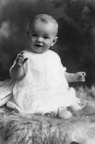 Monroe as an infant, wearing a white dress and sitting on a sheepskin rug