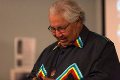 Photo of Justice Murray Sinclair during opening keynote. He is seen, while looking down and smiling, wearing a black top with multi-coloured accents.