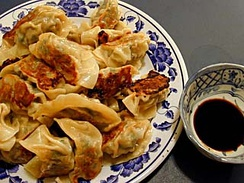A plate of potstickers (guotie) and dipping sauce