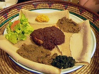 Typical Ethiopian and Eritrean cuisine: Injera (pancake-like bread) and several kinds of wat (stew)