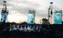 "Collins singing ""Land of Confusion"" at Knebworth, England in 1992. The song's music video features caricature puppets by the British television show Spitting Image. After Collins saw a caricatured version of himself on the show, he commissioned the show's creators, Peter Fluck and Roger Law, to create puppets of Genesis, as well as all the characters in the video.[183]"
