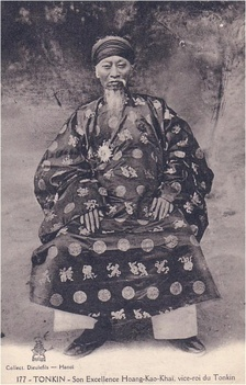 Aged man with cylindrical headdress, long flowing beard and moustache, a traditional Vietnamese tunic, darkly coloured with a light circular and Chinese character imprints, light coloured trousers, and dark shoes, sitting in a chair.