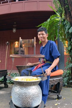 Thai man spools silk