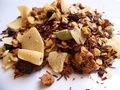 This retail mixture contains rooibos, coconut, ginger, cinnamon, apple, cardamom, black pepper and almond.