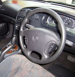 VX II Berlina interior displaying steering wheel command controls and a wood grain-faced transmission selection lever.