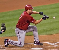 A man in a red baseball jersey and cap and gray baseball pants kneels on a dirt and grass field. He is holding a baseball bat flat in front of him in his hands with a ball approaching it.