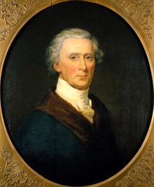 Oval portrait of a man from the bust up, facing the viewer. He has with gray hair and is wearing a blue jacket with a brown lapel, and white cravat around his neck.
