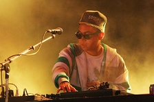 A DJ wearing a zip-up hoodie and checkerboard frame sunglasses