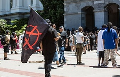 A crowd outside the California State Capitol after the riot. An anarchist flag is carried in the foreground. Debris lies on the plaza.