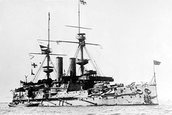 A large gray ship with blocky sides, two tall masts, and two funnels sits at anchor