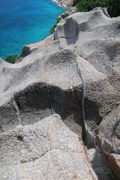 "Granite rock in the cliff of Gros la Tête on Aride Island, Seychelles. The thin (1–3 cm wide) brighter layers are quartz veins, formed during the late stages of crystallization of granitic magmas. They are sometimes called ""hydrothermal veins""."