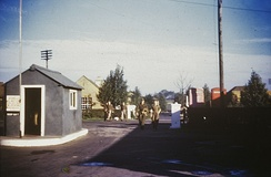 Main Entrance to Duxford Airfield during World War II. Officers and enlisted men are walking from the living site areas across the A505 Royston-Newmarket public road. The Officers' Mess building is on the extreme right, on the far side of the road. The sentry hut notice warns that military vehicles are not to leave the technical site unless on official business, This location is currently the staff entrance of IWM, Duxford.