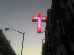 A 'Jesus Saves' neon cross sign outside of a Protestant church in New York City
