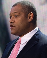 A man speaking in a black suit with a pink tie
