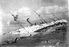 HMS Phoenix foundered alongside a coaling pier in Hong Kong after a typhoon in 1906.