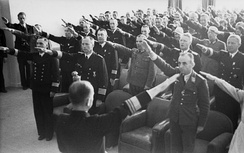 Black and white photograph of men wearing military uniforms with their right arms outstretched