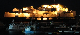 Castle Cornet seen at night over the harbour of St Peter Port.