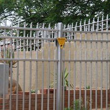 Residential electric palisade fence in Johannesburg, South Africa. The top spikes are electrified while the bottom of the palisade is grounded
