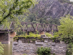 Railroad bridge and Maryland Heights opposite Harpers Ferry; also visible is the painted Mennen's Borated Talcum Toilet Powder advertisement on the cliffs, painted around 1903 to 1906.