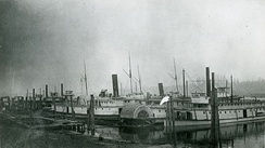 Olympian and Alaskan (steamers with schooner rigs, tall chimneys and walking beams) laid up in Portland, Oregon sometime before May 1889, at the OR&N steamboat boneyard.