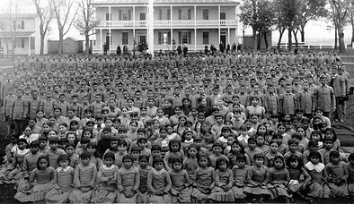 Native youth in front of Carlisle Indian Industrial School in Pennsylvania c. 1900