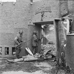 A Dutch school damaged by mortar fire, being searched for German snipers by Sergeant J. Whawell and Sergeant J. Turrell of the Glider Pilot Regiment. An empty CLE Canister lies open on the ground in the doorway of the school. 20 September 1944