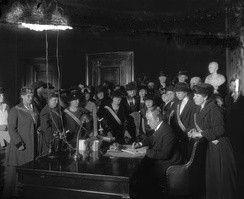 Madeline McDowell Breckinridge stands behind (second from the right) Governor Edwin P. Morrow as he signs Kentucky's ratification of the Nineteenth Amendment.