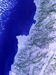 Image from space showing Jiyyeh oil slick in darkest blue, picture centered on Beirut. The largest oil spill in the history of the Mediterranean, it was caused by an Israeli air strike on Jiyeh power station[229] 10 August 2006
