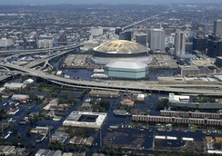 An aerial view of flooded areas of Central City and Central Business District, with the New Orleans Arena and the damaged Louisiana Superdome at center.