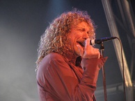 A man with long, curly hair wearing a red dress shirt and singing into a microphone on a stand.