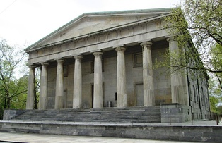 An old stone building with pillars. Classical Greek style architecture.