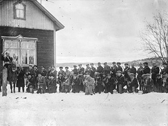 Around 40 troops of the paramilitary Red Guard pose to the camera next to a farmer's house on a field. One of them, their apparent commander, is on a horse.