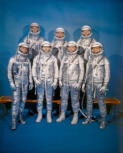 The Mercury Seven in 1960. Back row: Alan Shepard, Gus Grissom, Gordon Cooper; front row: Wally Schirra, Deke Slayton, John Glenn, Scott Carpenter. This was the only time they would appear together in pressure suits.[1] Slayton and Glenn are wearing spray-painted work boots.