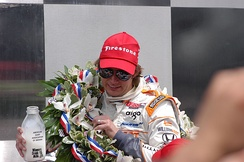 2011 Indianapolis 500 winner Dan Wheldon holding a bottle of milk.