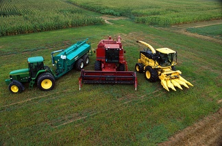 Agribusiness: a display of a John Deere 7800 tractor with Houle slurry trailer, Case IH combine harvester, New Holland FX 25 forage harvester with corn head