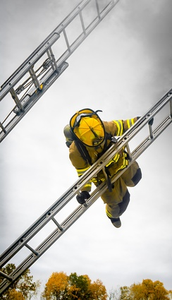 Firefighter carrying out a ladder slide