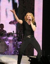A female blond performer singing to a microphone while lifting her left arm.